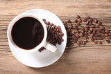 Coffee cup and coffee beans on old board - 231665310