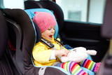 Adorable baby girl with blue eyes and in colorful clothes sitting in car seat. Toddler child in winter clothes going on family vacations and jorney. Safe travel, children safety, transportation - 231666161