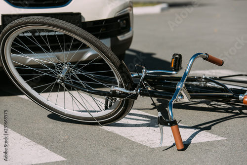 close up view of broken bicycle and car on road, car accident concept - 231668575