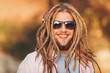 Portrait of hipster blonde bearded boy with dreads wearing headphones and glasses walking and smiling outdoors an the sunny autumn day