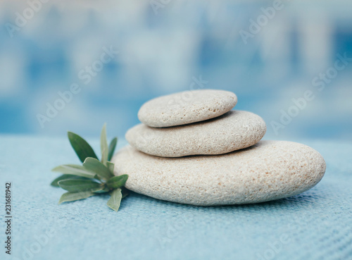 Zen stones tower. White spa stones with leaves on blurred blue background.