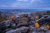 Frau guckt auf Sonnenuntergang vom Felsen, Dürenther Klippen, Blauestunde, Landschaft mit Nebel und Windmühlen am Horizont - 231685511