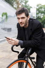 """Постер, картина, фотообои """"Handsome young man dressed in coat leaning on a bicycle"""""""