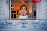 Woman standing in front of fridge with head in hands and looking at cheesecake. Picture taken from the inside of fridge. - 231690719