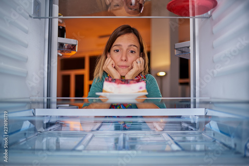 Poster Woman standing in front of fridge with head in hands and looking at cheesecake. Picture taken from the inside of fridge.