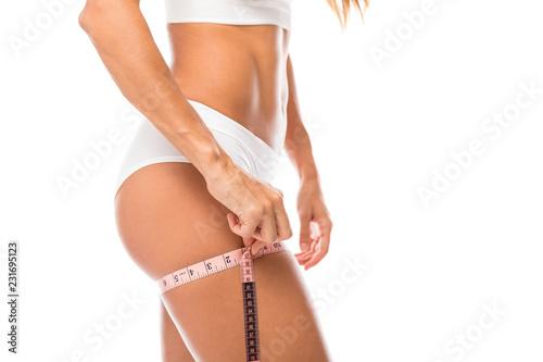 Leinwandbild Motiv Woman With Slim Body Taking Thigh Measurements