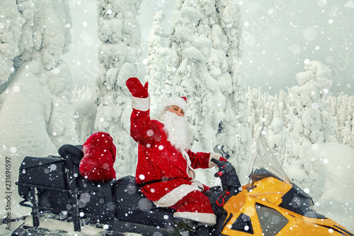 obraz lub plakat Authentic Santa Claus is riding a snowmobile through the winter forest.