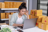 stressed woman working with laptop computer and courier parcel box at home office - 231697982