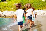 Kids running away along sandy beach in summer