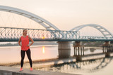 Confident strong cute sporty blond girl standing on jetty near river after early morning training. - 231699595