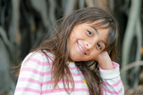 Happy beautiful young girl in front of a big tree at night - 231700792