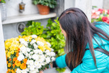 Close-up of a Sad Woman Holding Fowers in front of a Loved one's Gravestone - 231702317