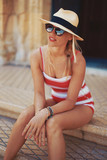 Young stylish woman sitting on steps on mediterranean street - 231702941