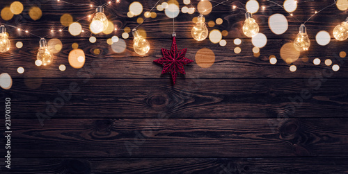 Empty, dark wooden background illuminated by retro light bulbs, with copy space  - 231703150
