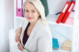 Modern businesswoman. Beautiful middle aged woman looking at camera with smile while siting in the office. - 231705588