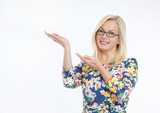 Friendly smiling middle aged woman pointing at copyspace isolated - 231705926