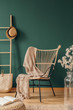 Wicker armchair with beige blanket, real photo with copy space on empty green wall