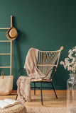Wicker armchair with beige blanket, real photo with copy space on empty green wall - 231706779