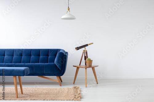 Niebieska kanapa z aksamitu obok drewnianego stolika do kawy z kaktusa w doniczce i teleskopie, prawdziwe zdjęcie z miejsca na kopię na pustej białej ścianie i naturalny dywan na podłodze