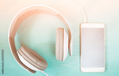 Headphones and smartphone on the wooden desk, toned - 231707527