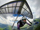 Aerial shot of brave extreme hang glider pilot soaring the thermal updrafts above mountains - 231709356