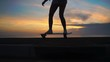 Silhouette of a skateboarder against the sunset sky in slow motion steadicam shot