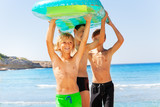 Happy boys with air mattress overhead on the beach