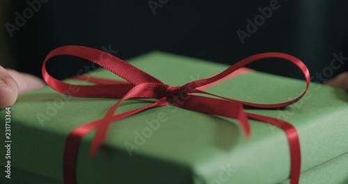 Foto Murales Closeup red ribbon bow on green gift box