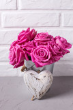 Bright pink roses flowers in bucket and  heart on grey background against white wall. - 231714190