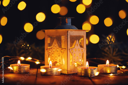 Leinwanddruck Bild Christmas lantern with four candles and lights on a wooden board