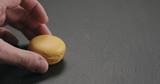 man hand put orange macaron on slate board - 231715970