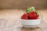 Fresh strawberries in white bowl on wood background with copy space