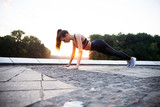 Fit girl doing plank exercise outdoor in the park warm summer day. Concept of endurance and motivation. - 231723110
