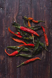 Dried hot red and green chili peppers on brown textured wood - 231723536