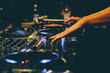Dj hands on a mixer and turntables with the vinyl