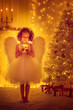 Leinwanddruck Bild - Christmas Angel Child with Wings hold Lighting Candle front of Xmas Tree, New Year Night