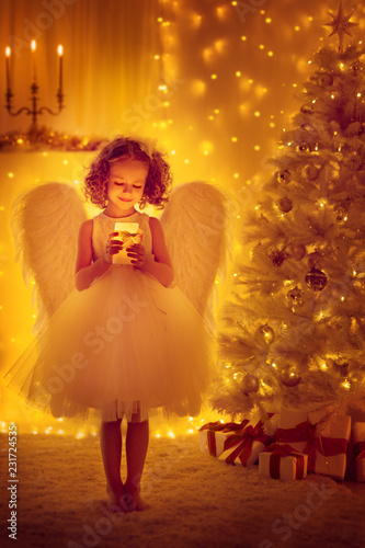 Christmas Angel Child with Wings hold Lighting Candle front of Xmas Tree, New Year Night © inarik