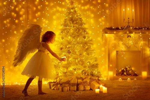 Choinka i Anioł Dziecko ze świecą, dziewczyna dekorowanie prezenty w pokoju z kominkiem