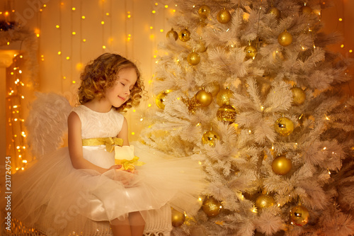 Leinwanddruck Bild Child Dream under Christmas Tree, Happy Girl with Candle Sitting in Fantasy Night Decorated Room