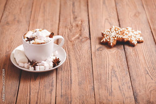 Poster Christmas or new year background. A Cup of festive hot chocolate or cocoa with marshmallows and traditional handmade gingerbread on the table. The concept of advertising cocoa drink. Copy space