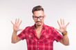Emotions and people concept - handsome man showing you his hands or scares you, wearing checkered shirt and glasses on white background.