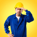 Young workman with helmet looking far away with hand to look something on yellow background - 231739987