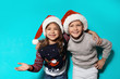 Leinwanddruck Bild - Cute children in warm sweaters and Christmas hats on color background