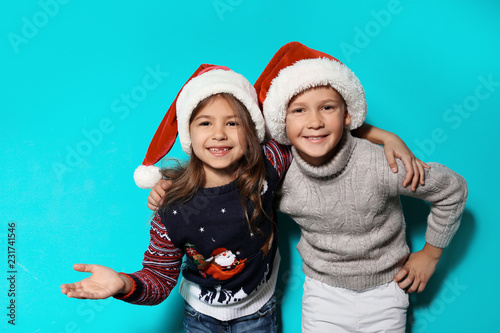 Leinwanddruck Bild Cute children in warm sweaters and Christmas hats on color background