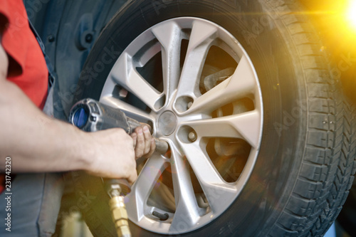 Mechanic changing a car tire in a workshop on a vehicle on a hoist using an electric drill to loosen the bolts in a concept of service or replacement - 231742320
