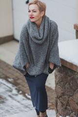 cute woman in gray sweater is standing in yard © glebchik