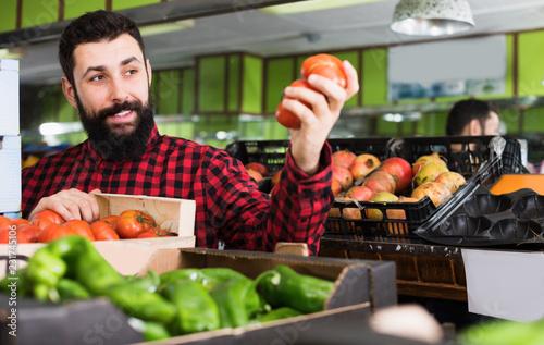 Leinwanddruck Bild Smiling male seller showing tomatoes in store