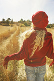 Back view of a young woman in nature in a sunny autumn day - 231746153