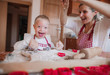 Leinwanddruck Bild - A laughing handicapped down syndrome child with his mother indoors baking.