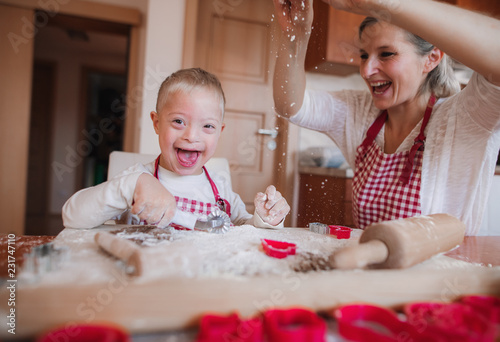 Leinwanddruck Bild A laughing handicapped down syndrome child with his mother indoors baking.